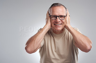 Buy stock photo Shot of a mature man standing against a grey background in the studio and covering his ears with his hands