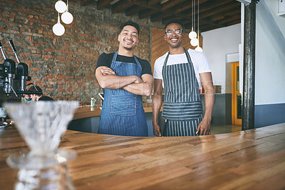 Buy stock photo Shot of two confident young men working in a cafe