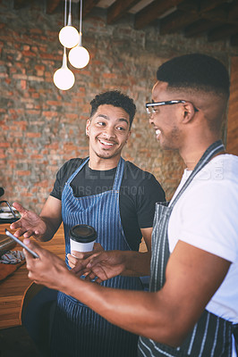 Buy stock photo Shot of two young men using a digital tablet while making coffee at a cafe