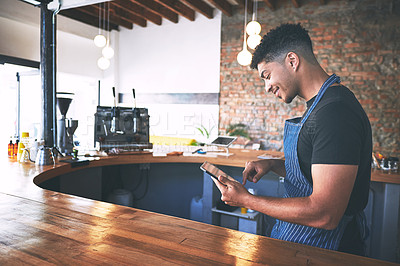 Buy stock photo Shot of a confident young man using a digital tablet while working in a cafe