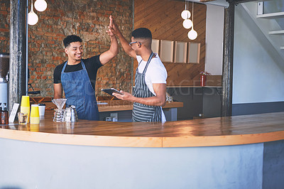 Buy stock photo Shot of two confident young men using a digital tablet and giving each other a high five while working in a cafe