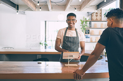 Buy stock photo Shot of a young man buying coffee in a cafe