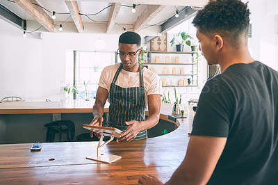 Buy stock photo Shot of a young man using a digital tablet while buying coffee in a cafe