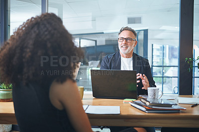 Buy stock photo Shot of a mature businessman having a meeting with his coworker in the boardroom of a modern office