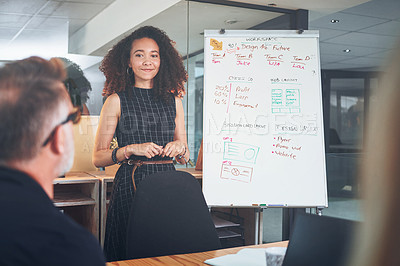 Buy stock photo Shot of a young businesswoman delivering a presentation to her coworkers in the boardroom of a modern office
