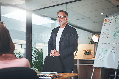 Buy stock photo Shot of a mature businessman delivering a presentation to his coworkers in the boardroom of a modern office