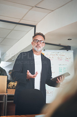 Buy stock photo Shot of a mature businessman using a digital tablet while delivering a presentation in the boardroom of a modern office