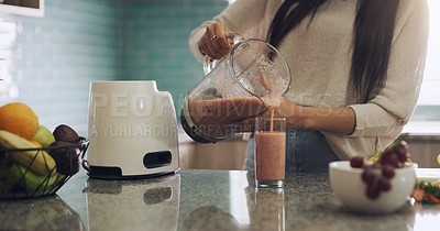 Buy stock photo Shot of an anonymous woman preparing a smoothie in her kitchen at home