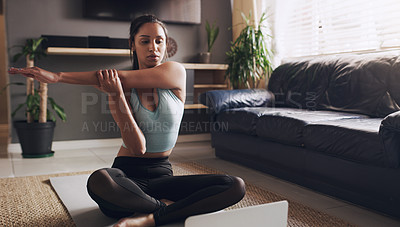 Buy stock photo Shot of a young woman stretching before a workout at home