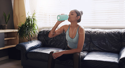 Buy stock photo Shot of a young woman cooling down completing her workout routine at home