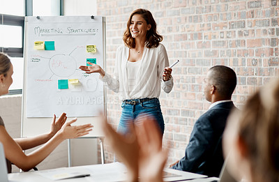 Buy stock photo Shot of an attractive young businesswoman standing and using a visual aid for a presentation to her coworkers