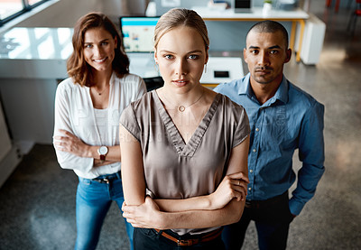 Buy stock photo Shot of a diverse group of businesspeople standing together in the office with their arms folded during the day