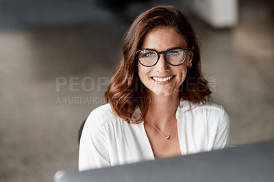 Buy stock photo Shot of an attractive young businesswoman sitting alone in the office and using her computer