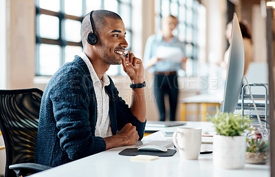 Buy stock photo Shot of a young businessman wearing a headset while working on a computer in an office