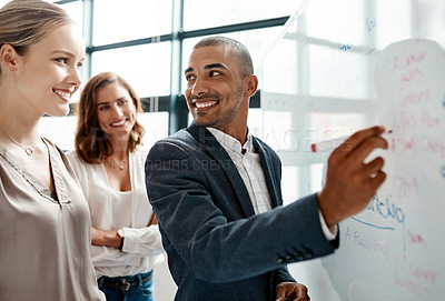 Buy stock photo Shot of a young businessman brainstorming on a whiteboard with his colleagues in an office
