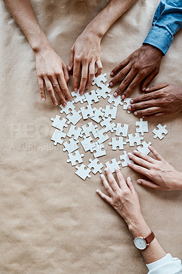 Buy stock photo High angle shot of a group of unrecognisable businesspeople joining puzzle pieces together in an office