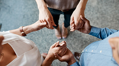 Buy stock photo High angle shot of a group of unrecognisable businesspeople holding hands while standing together in a huddle