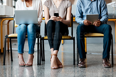Buy stock photo Closeup shot of a group of unrecognisable businesspeople using digital devices while sitting in a row in an office