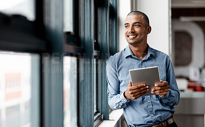 Buy stock photo Shot of a young businessman using a digital tablet while standing at a window in an office