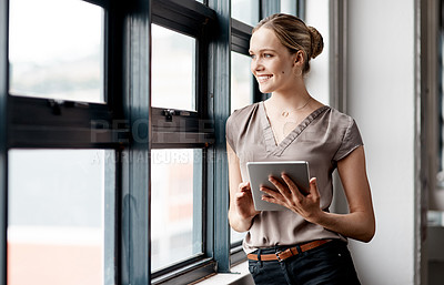 Buy stock photo Shot of a young businesswoman using a digital tablet while standing at a window in an office