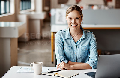Buy stock photo Shot of a young businesswoman using a laptop and making notes in a modern office
