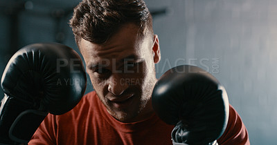 Buy stock photo Cropped shot of a young man wearing boxing gloves during his workout at the gym