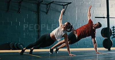 Buy stock photo Shot of a young couple raising their arms while doing pushups at the gym