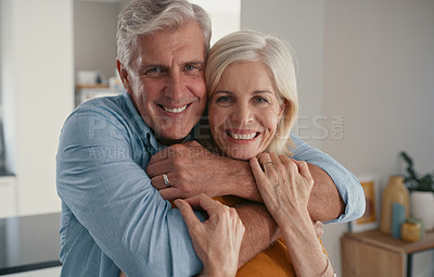 Buy stock photo Shot of a mature couple standing together with their arms around each other during the day at home