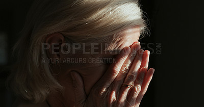 Buy stock photo Shot of a mature woman sitting alone in a dark room at home and feeling depressed