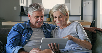 Buy stock photo Shot of a mature couple sitting on the sofa at home together and using a digital tablet