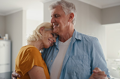 Buy stock photo Shot of a mature couple sharing an intimate moment by dancing together in their home