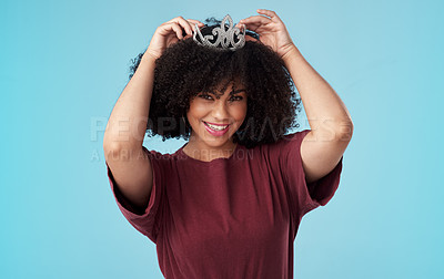 Buy stock photo Studio shot of a young woman putting a crown her head against a blue background