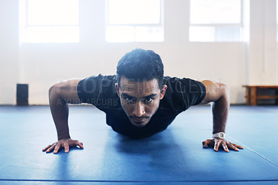 Buy stock photo Shot of a young man doing pushups as a part of his workout routine at the gym