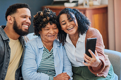 Buy stock photo Shot of a young man and woman taking selfies with their elderly relative on the sofa at home