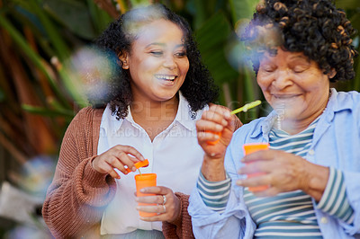 Buy stock photo Shot of a young woman blowing bubbles with her elderly relative in a garden