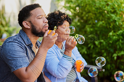 Buy stock photo Shot of a young man blowing bubbles with his elderly relative in a garden
