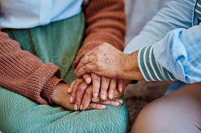 Buy stock photo Shot of an unrecognisable woman holding hands with her elderly relative on the sofa at home