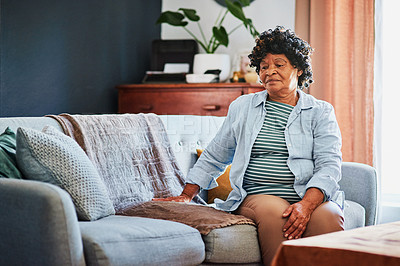 Buy stock photo Shot of an elderly woman looking unhappy on the sofa at home