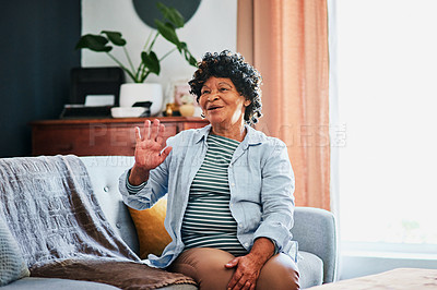 Buy stock photo Shot of an elderly woman waving on the sofa at home