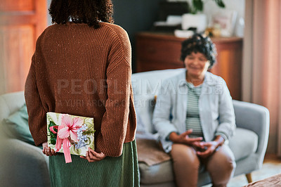 Buy stock photo Shot of a young woman giving her elderly relative a present at home