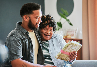 Buy stock photo Shot of a young man giving his elderly relative a present on the sofa at home