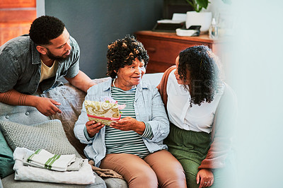 Buy stock photo Shot of a young man and woman giving their elderly relative a present on the sofa at home
