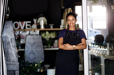 Buy stock photo Cropped portrait of an attractive young woman standing with her arms crossed in the doorway to her flower store
