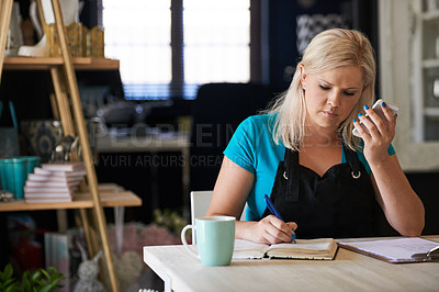 Buy stock photo Cropped shot of an attractive young woman working in her flower store and taking notes while on the phone