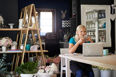 Buy stock photo Cropped shot of an attractive young woman sending a text message while working in her flower shop