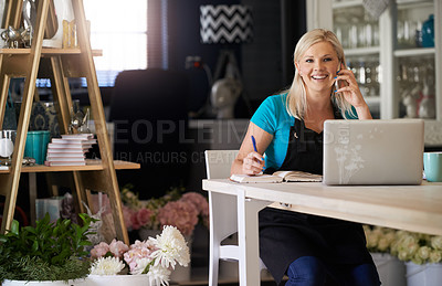 Buy stock photo Cropped portrait of an attractive young woman working in her flower store and taking notes while on the phone