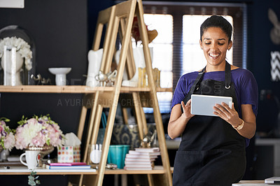 Buy stock photo Cropped shot of an attractive young woman using a tablet while working in her flower shop