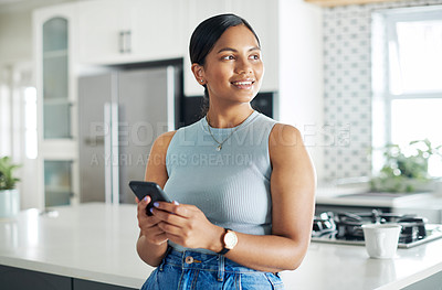 Buy stock photo Shot of an attractive young woman standing alone in her kitchen and using her cellphone