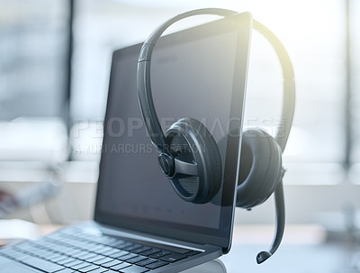 Buy stock photo Shot of a set of headsets resting on a laptop in an empty office during the day