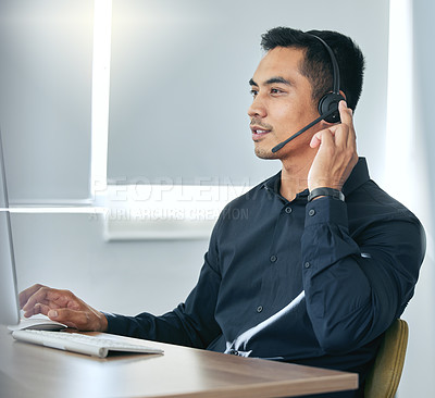 Buy stock photo Shot of a handsome young salesman sitting alone in his office and wearing a headset while using his computer